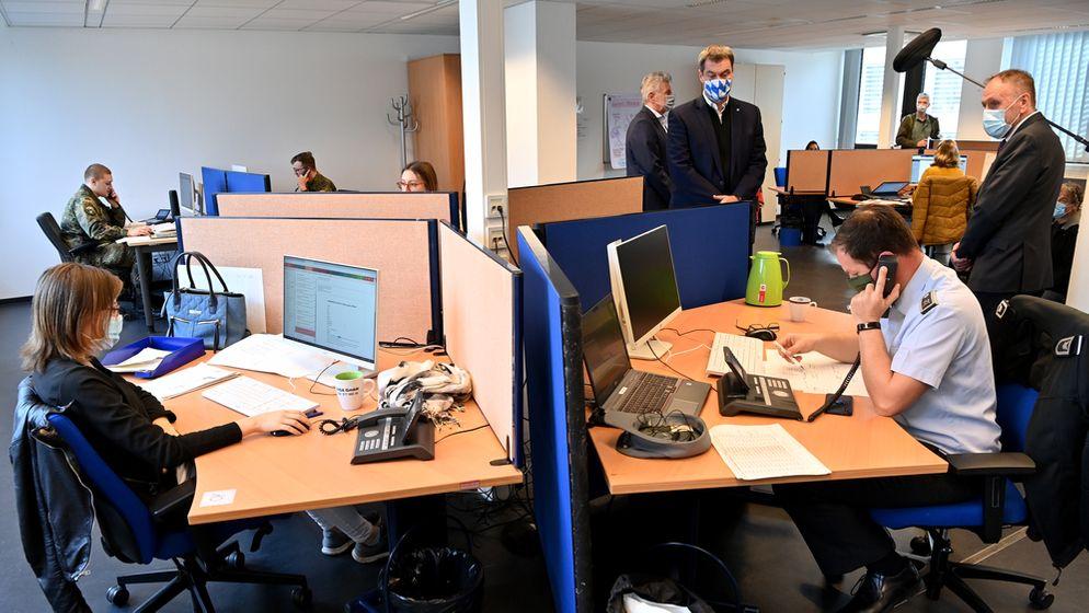 Ministerpräsident Söder (blau-weißer Mund-Nasen-Schutz) bei der Kontaktnachverfolgung im Münchner Gesundheitsamt am 22.10.20 | Bild:pa/dpa/Peter Kneffel
