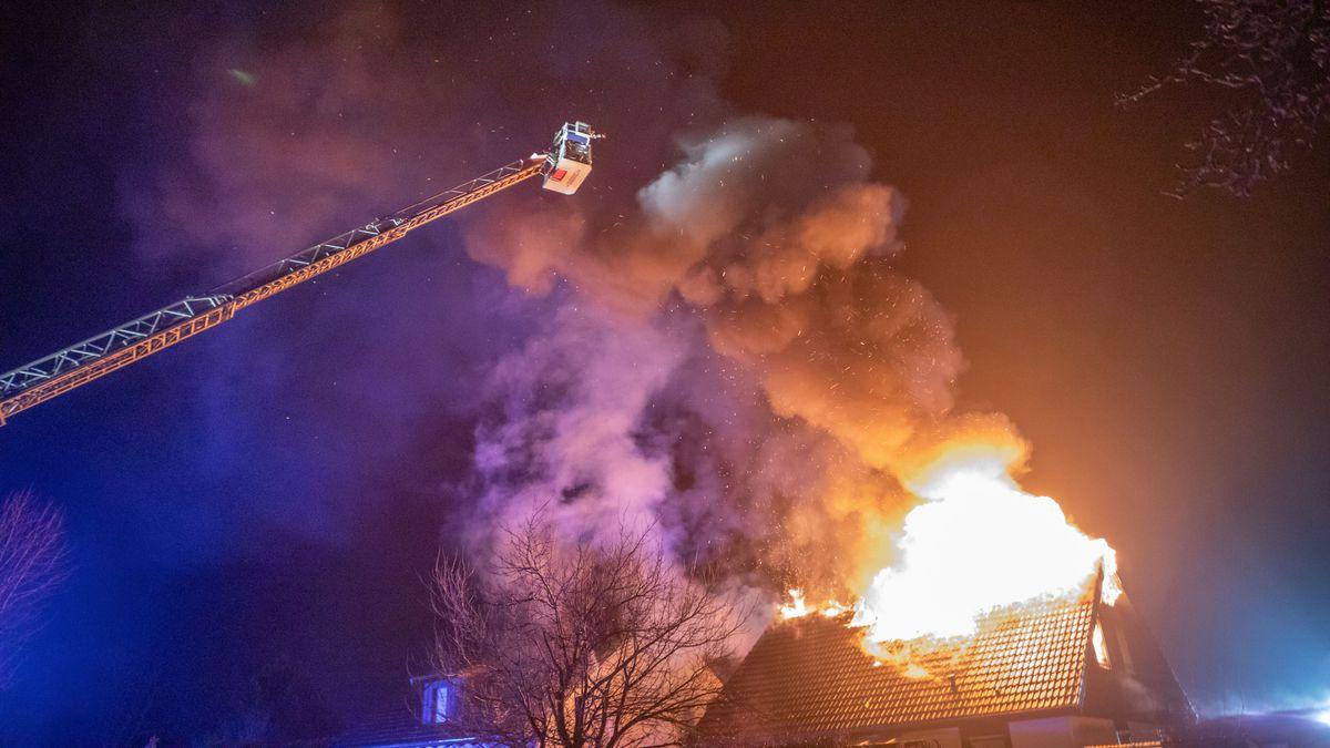 Feuerwehrleute im Korb einer Drehleiter bekämpfen den Brand eines Hauses von oben