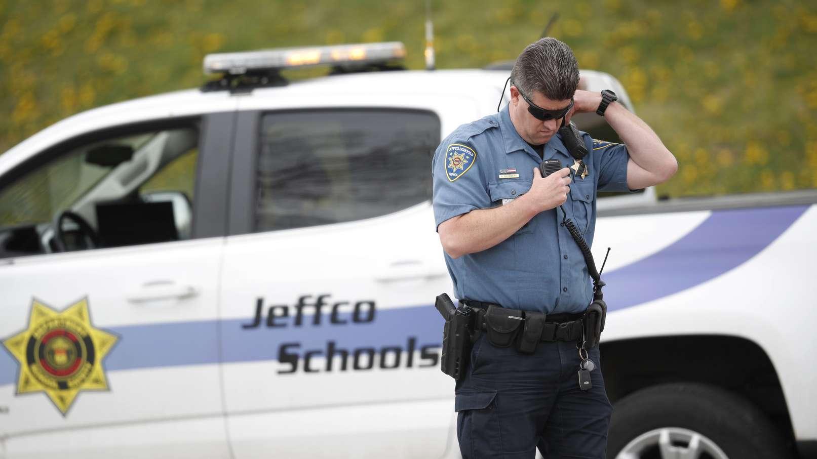 USA, Littleton: Ein Polizist steht vor der Columbine High School, während Schüler diese verlassen.