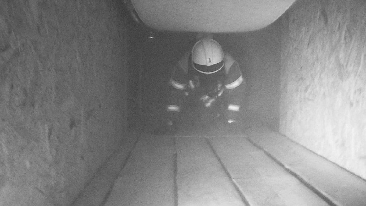 Feuerwehrmann mit Atemschutz beim Training in einem dunklen Tunnel
