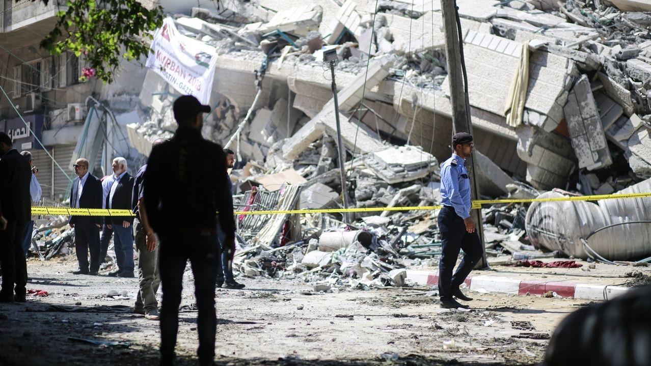 Palästinensische Autonomiegebiete: Polizisten und Einsatzkräfte stehen am 05.05.2019 in Gaza-Stadt vor den Trümmern eines Gebäudes, welches bei israelischen Luftangriffen auf die Stadt zerstört wurde.