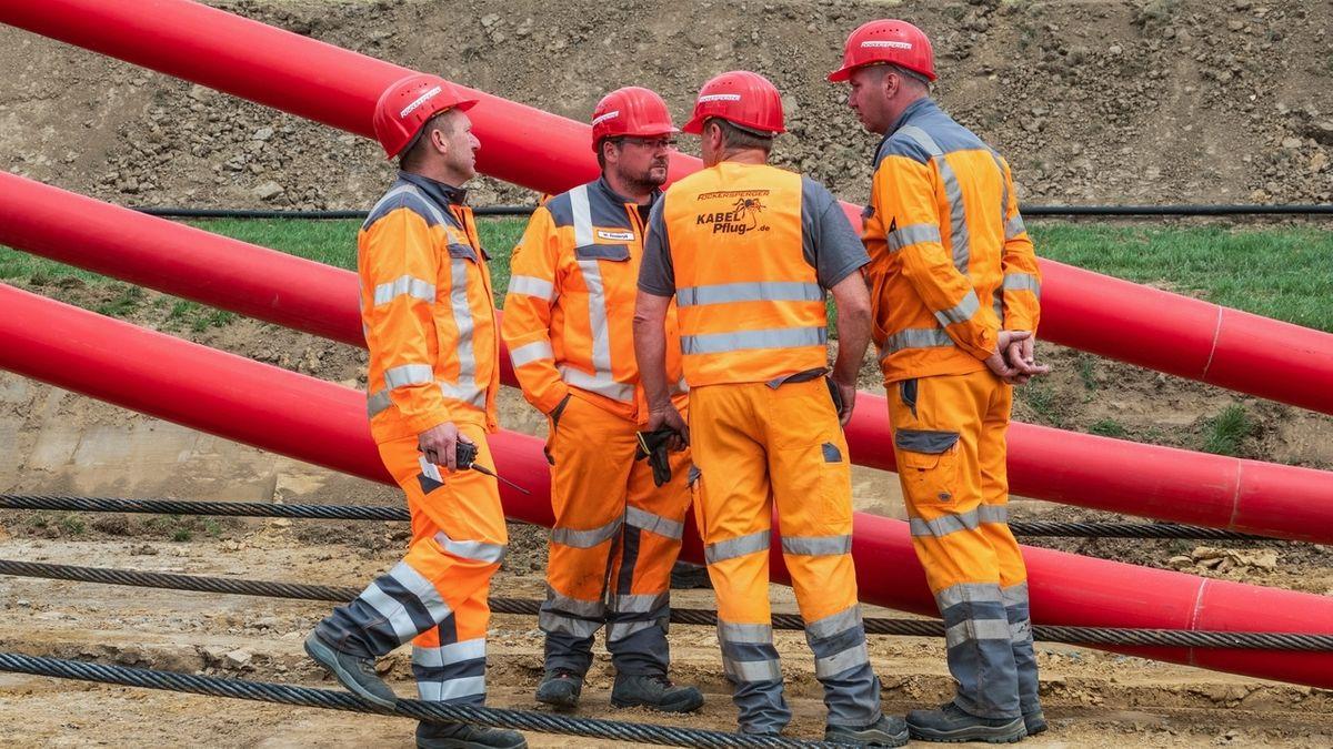 Arbeiter in orangene Anzügen stehen vor dicken roten Kabeln, die in den Boden verlegt werden.