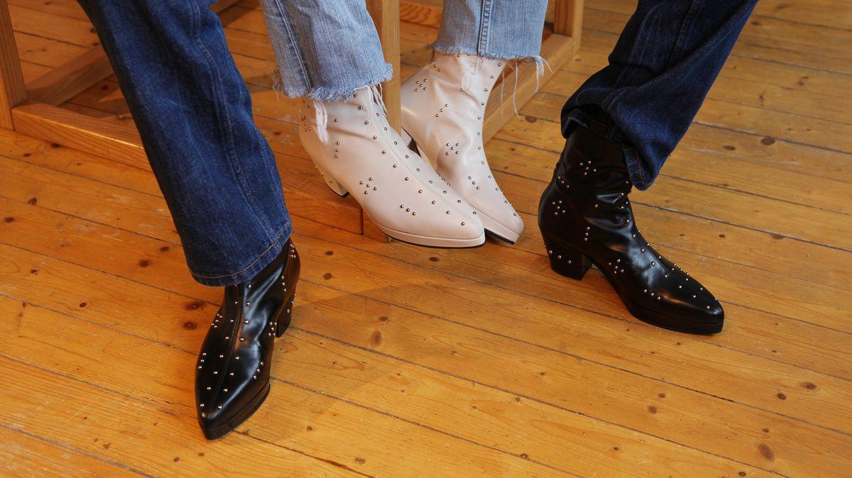 Nahaufnahme auf die Beine von zwei Menschen die Stiefel im Cowboy-Look tragen. Die einen weiß, die anderen schwarz, beide haben Metallapplikationen.