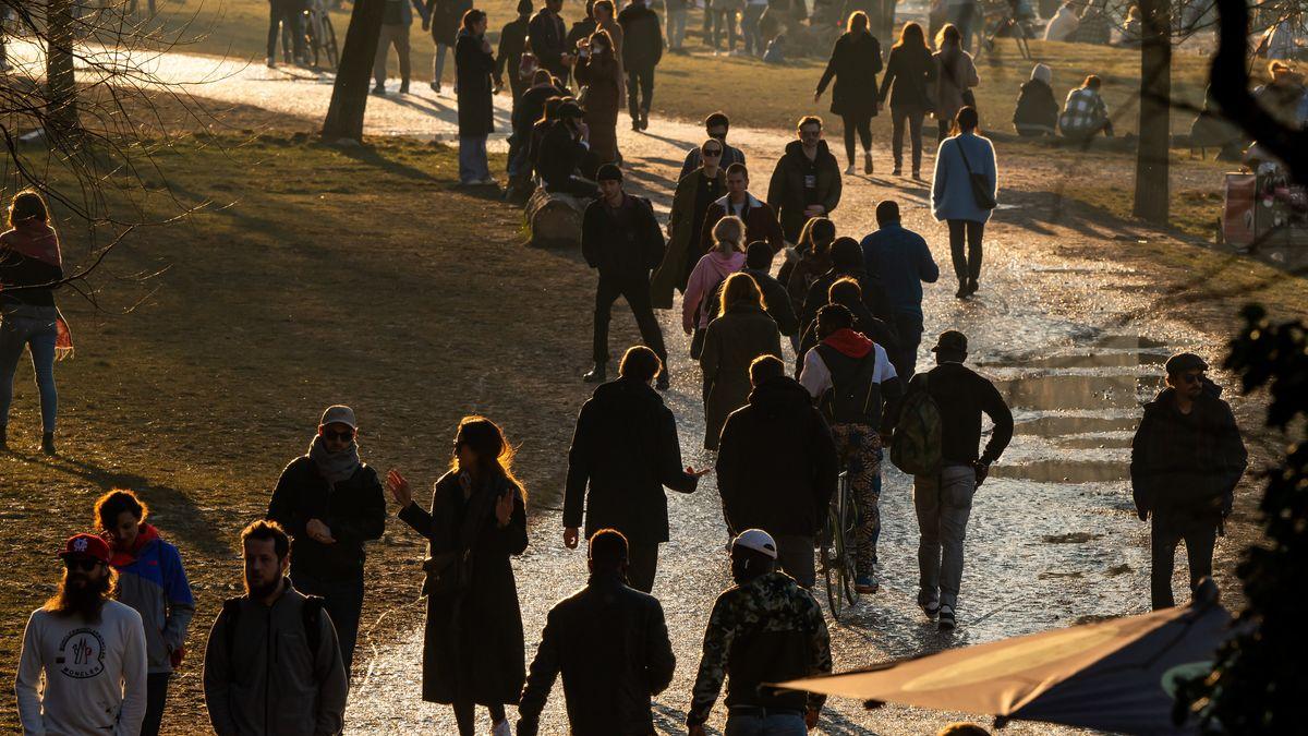 Menschen laufen an der Münchner Isar durch die Sonne.