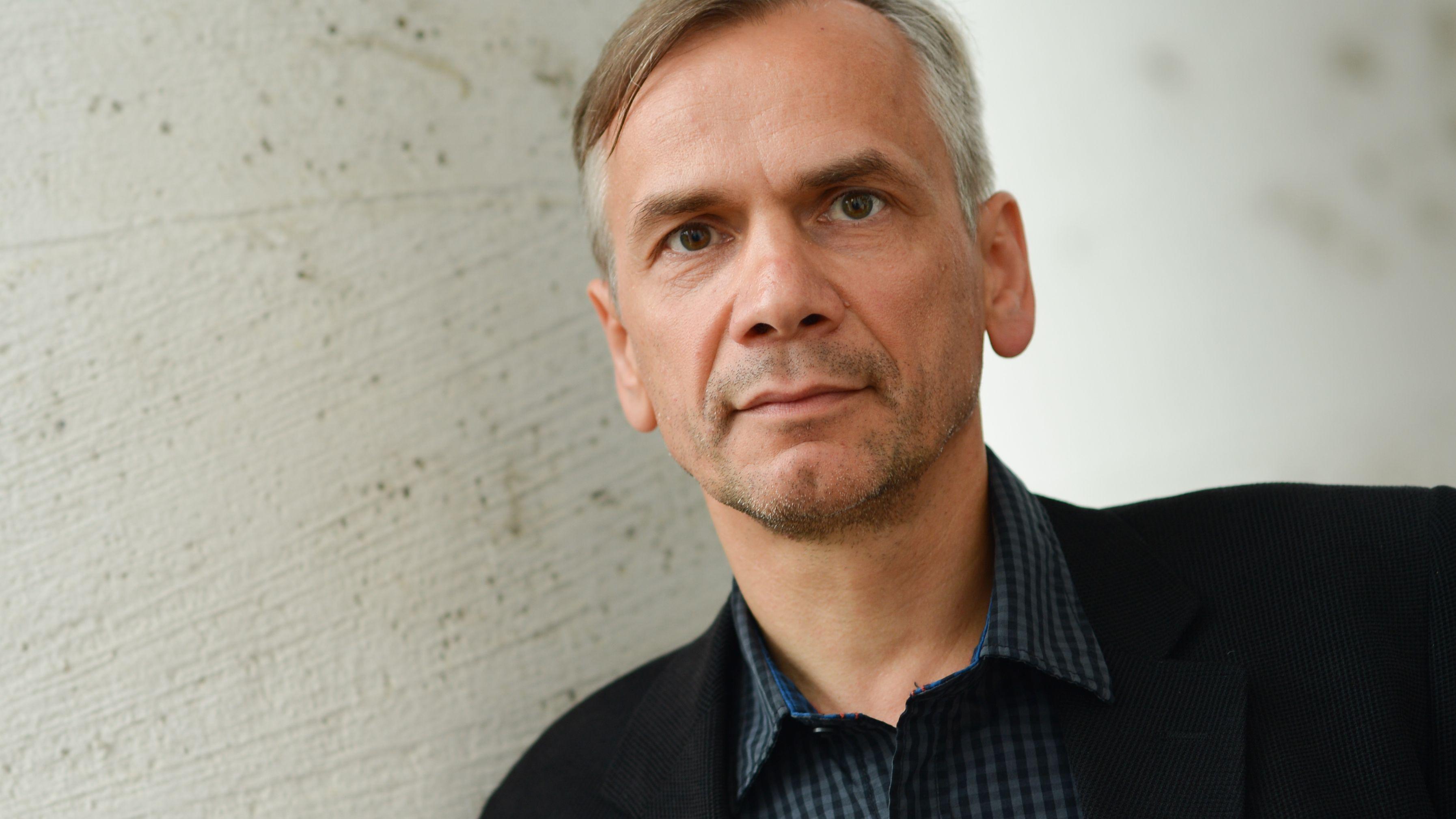 Autor Lutz Seiler blickt, neben einer verputzten Wand stehend, in die Kamera