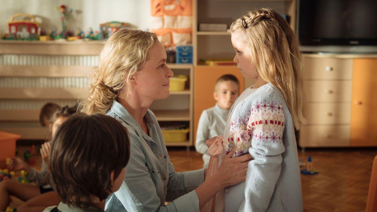 """Eine Frau sitzt in einer Einrichtung für Kinder vor einem kleinen Mädchen und strahlt es an: Szene aus """"Pelikanblut"""""""