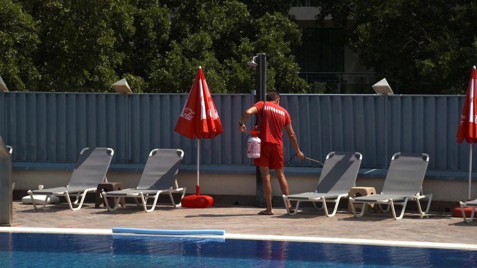 """Mann mit """"Lifeguard""""-Tshirt desinfiziert graue Sonnenliegen."""