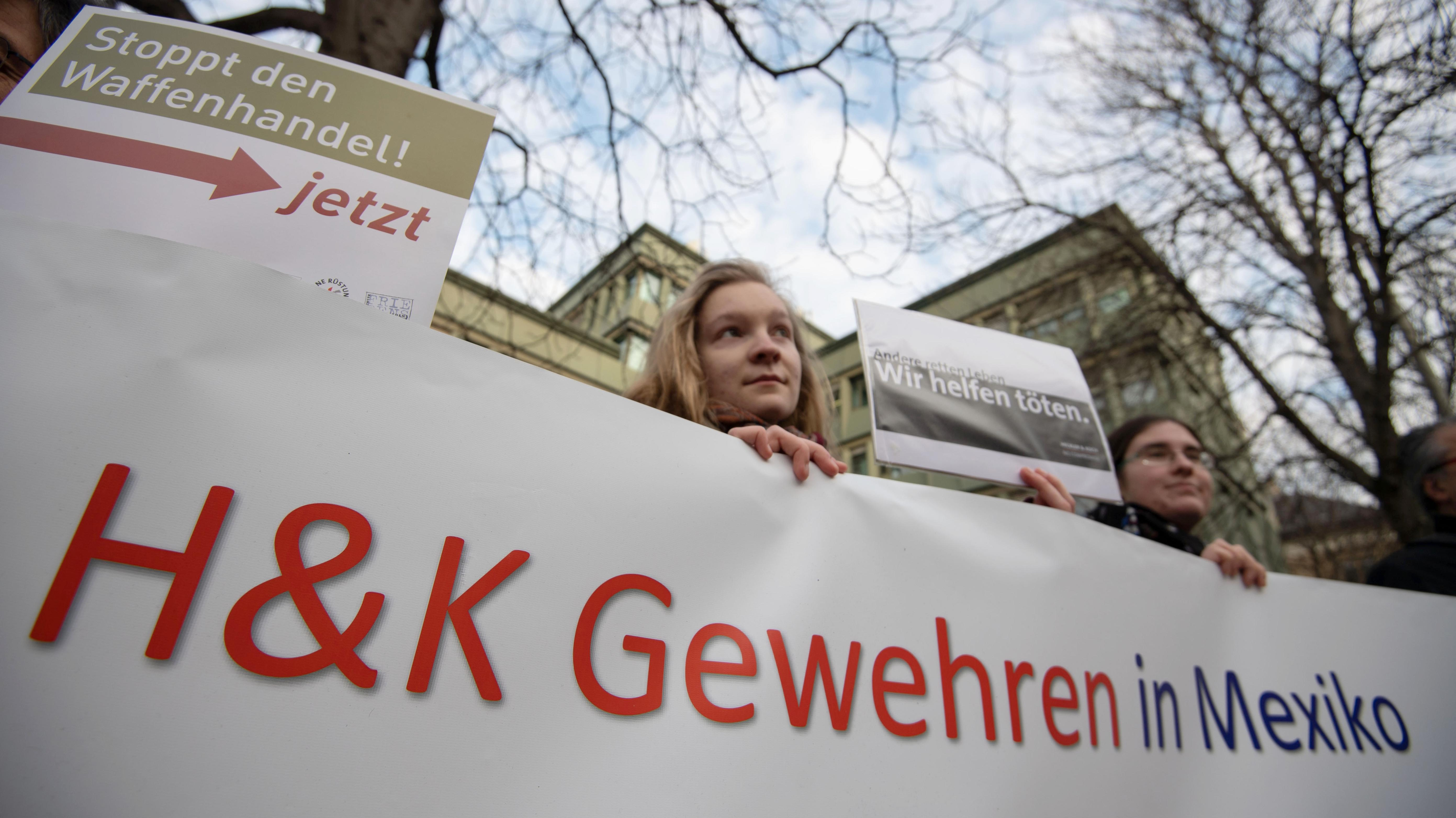 Demonstranten stehen vor der Urteilsverkündung im Prozess gegen ehemalige Mitarbeiter von Heckler & Koch vor dem Landgericht Stuttgart.