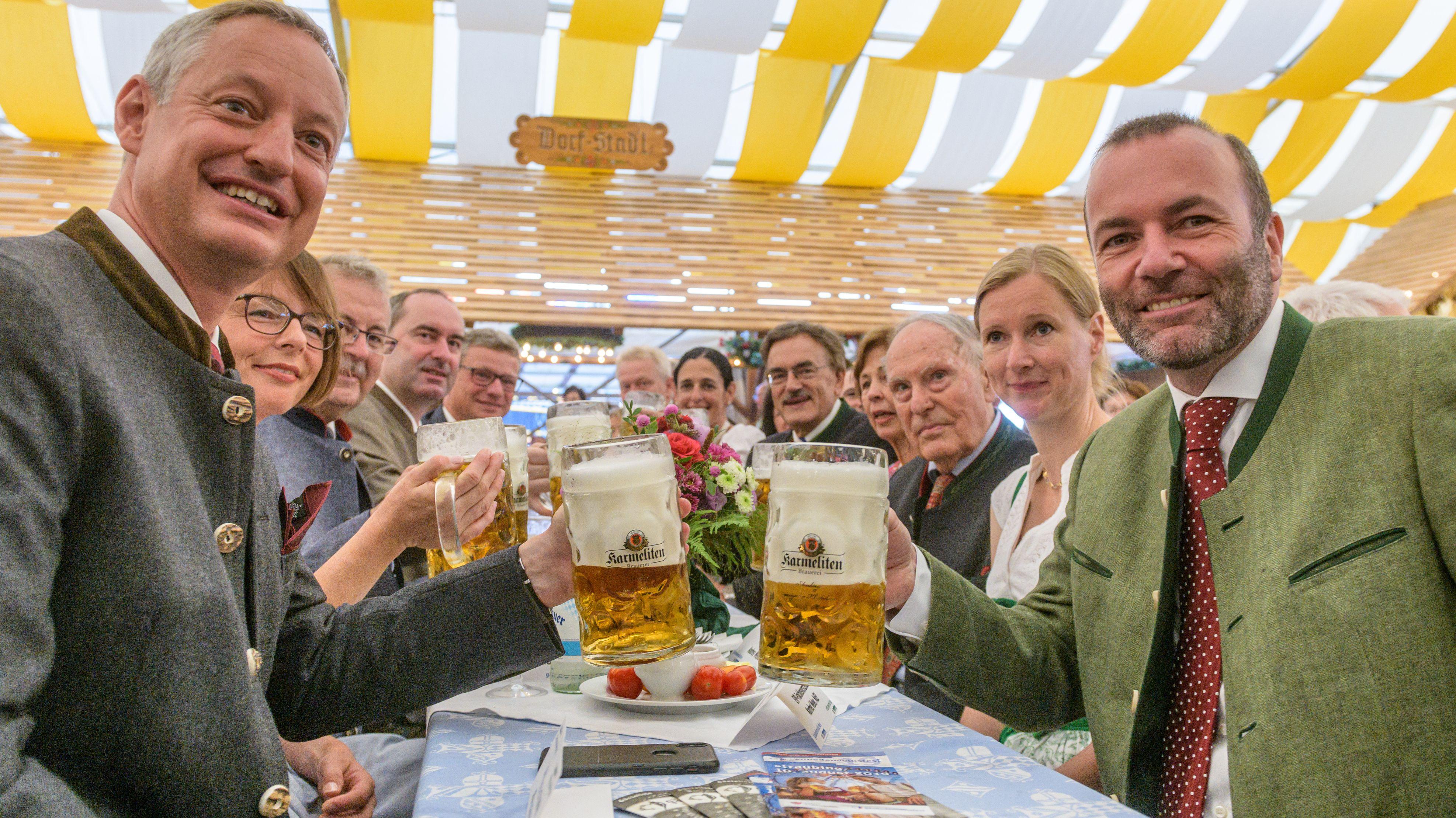 Manfred Weber, EVP-Fraktionschef (r), und Markus Pannermayr (CSU), OB von Straubing, prosten sich beim Gäubodenvolksfest mit Bierkrügen zu.