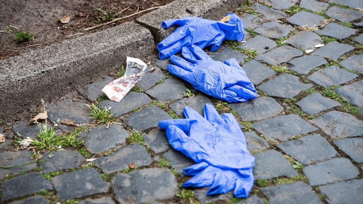 Gebrauchte Schutzhandschhe liegen auf Pflastersteinen