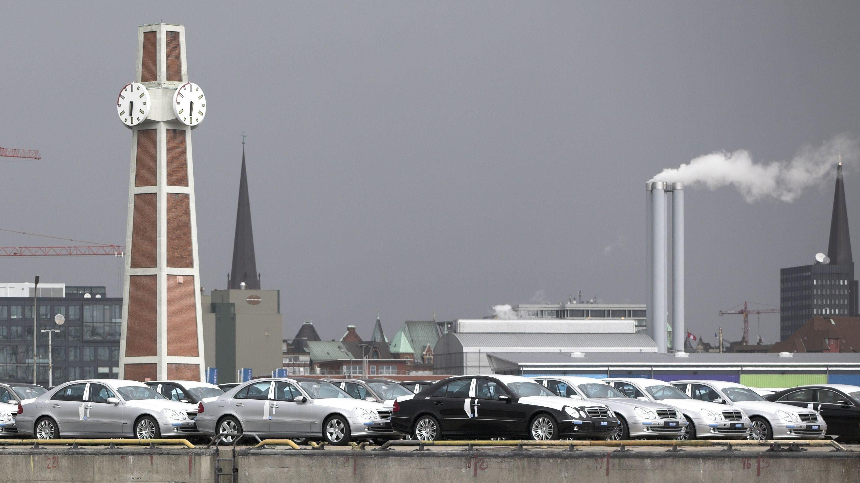 Schwarze und silberne Autos die mit Folien beklebt sind stehen an einer Hafenkante. Dahinter ein Uhrenturm und rauchende Kamine.
