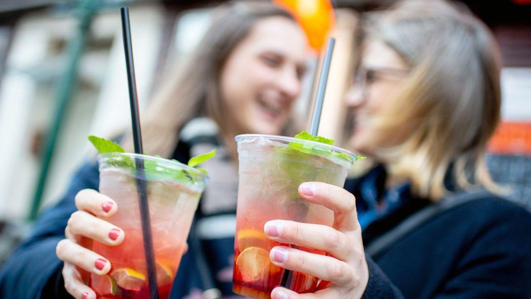 Zwei Frauen stoßen vor einer Bar mit einem Erdbeer-Mojito an (Symbolbild).
