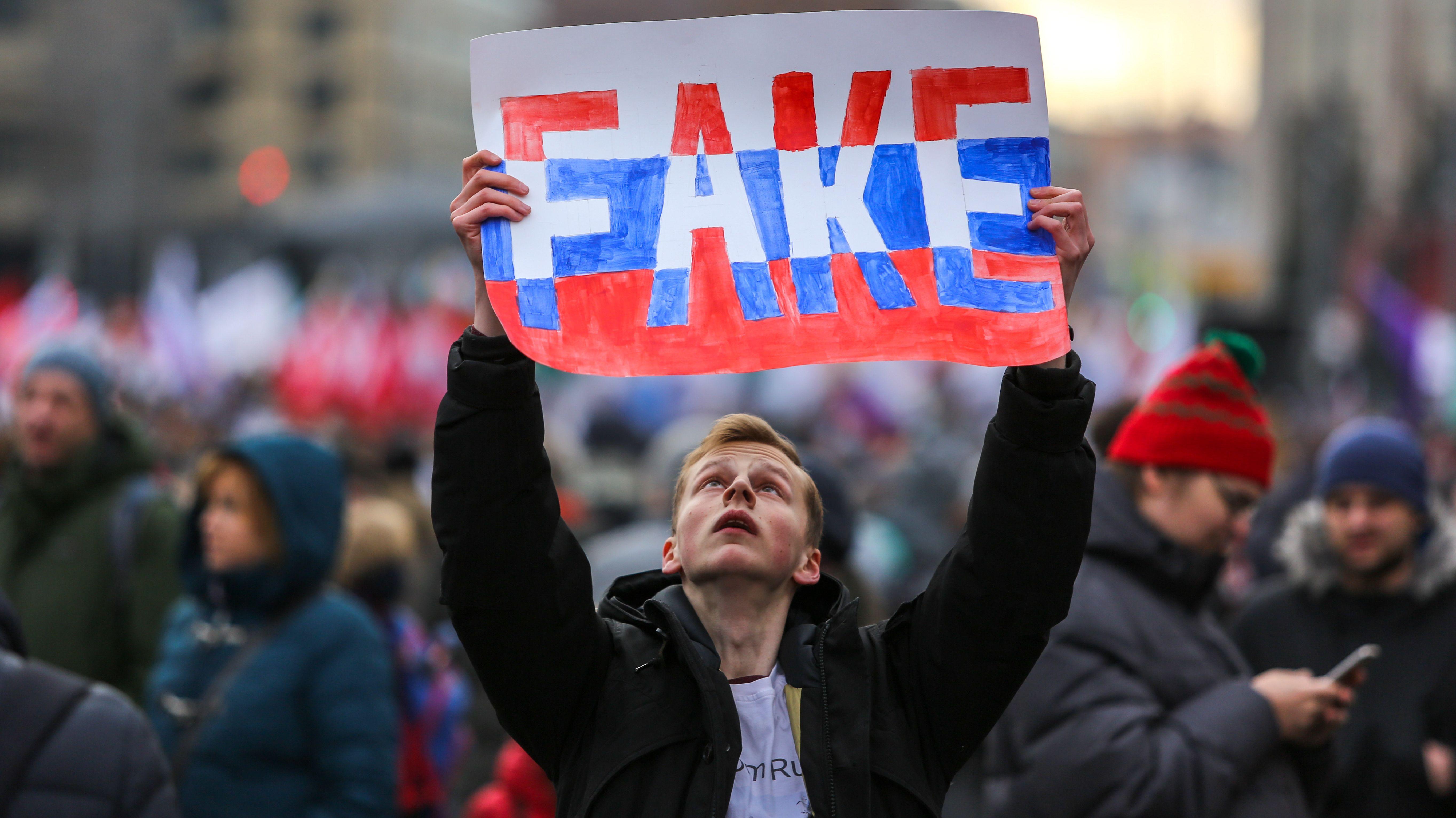 """Ein junger Mann hält ein Schild mit dem Wort """"Fake"""" in die Luft - in den Farben der russischen Flagge."""