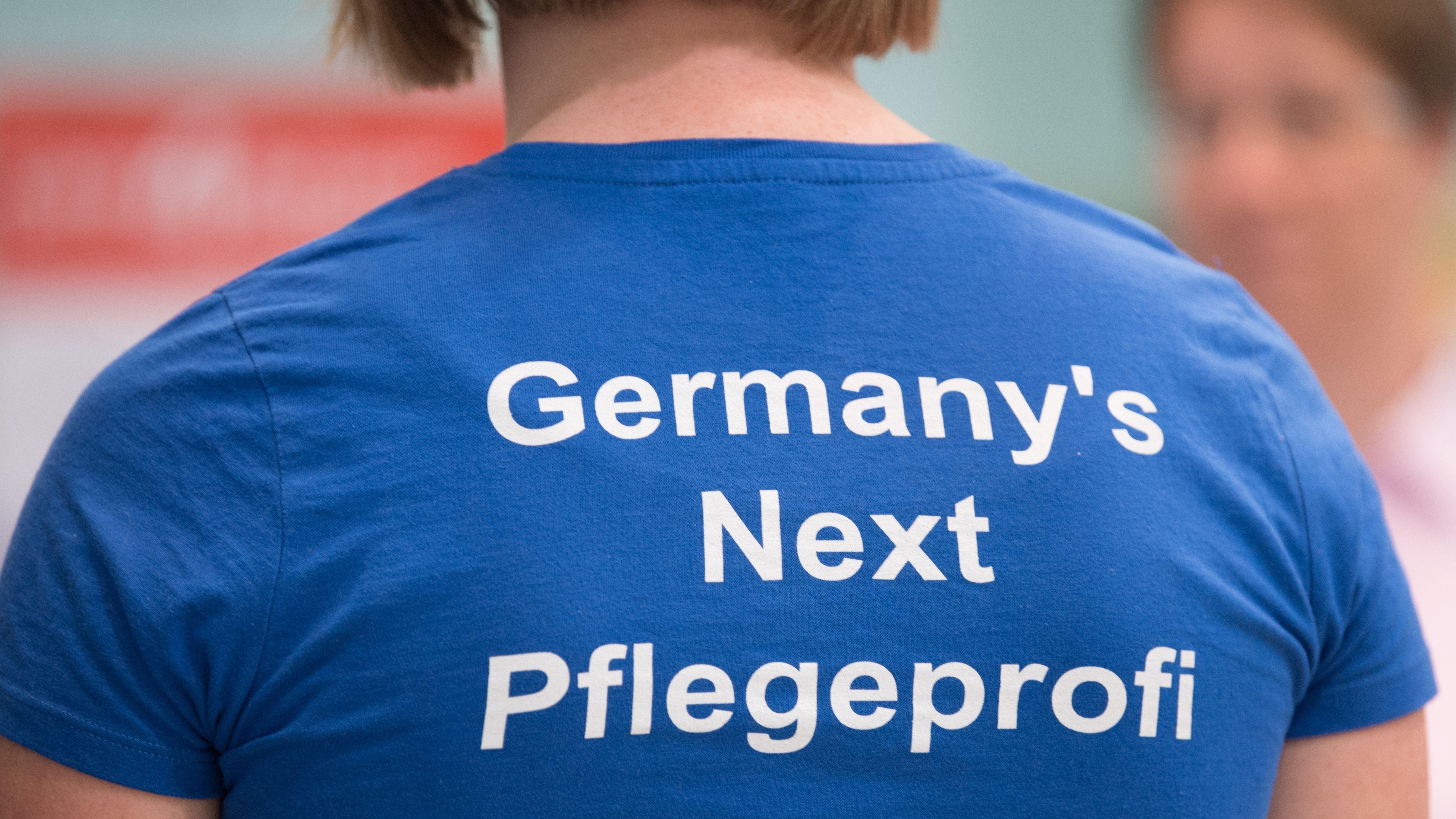"""Teilnehmerin des 13. Pflegedialoges trägt ein T-Shirt mit der Aufschrift """"Germany's Next Pflegeprofi"""""""