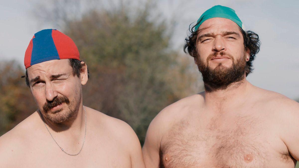 Zwei Männer mit Badekappe und nacktem Oberkörper blicken in die Kamera