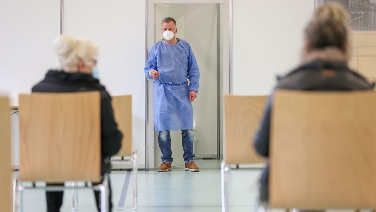 Ein Impfarzt bittet den nächsten Patienten in eine Impfkabine (Symbolbild)