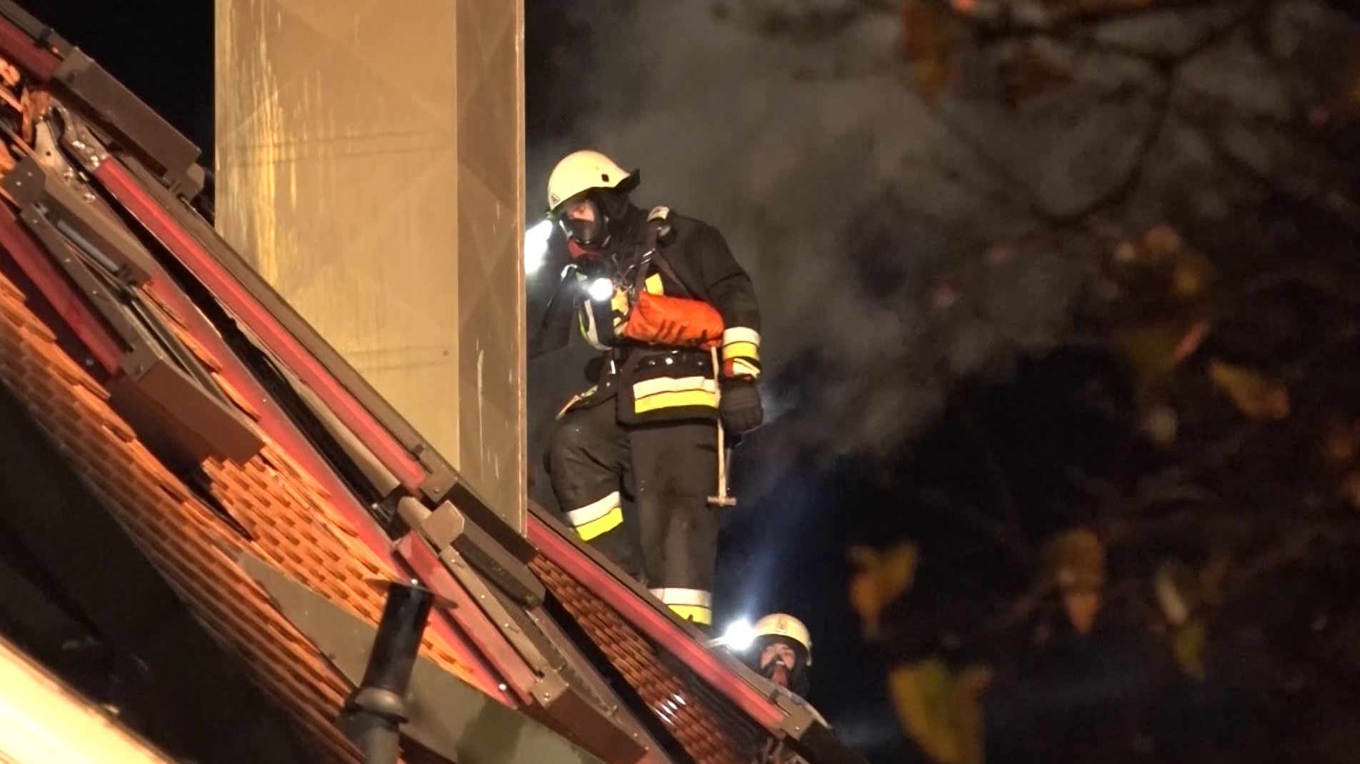 Feuerwehrleute auf dem Dach des brennenden Einfamilienhauses in Mainburg