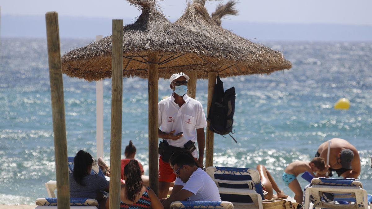 Der Mitarbeiter eines Strandliegenverleihs steht mit einer Mund-Nasen-Schutz-Maske unter einem Sonnenschirm am Son Maties Strand auf Mallorca.