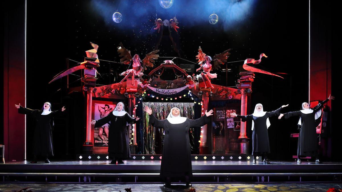 Rot beleuchtete Bühne mit Putten und geschwungenen Spruchbändern