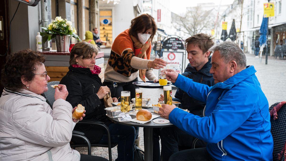 Eine Wirtin bringt ihren Gästen auf die Terrasse vor ihrer Kneipe in Saarbrücken Getränke. Seit dem 06.04.2021 dürfen Gastronomen im Rahmen des Saarland Modells unter Auflagen ihre Außengastronomie wieder öffnen.