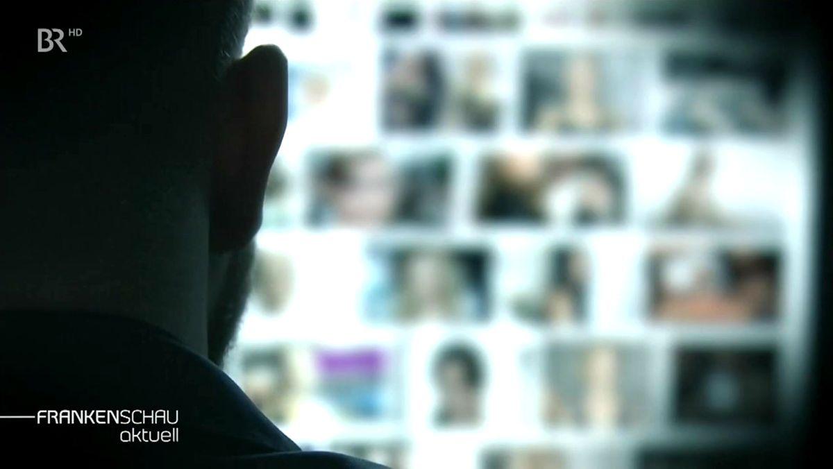 Ein Mann schaut auf einen Bildschirm, auf denen mehrere Menschen verschwommen abgebildet sind.
