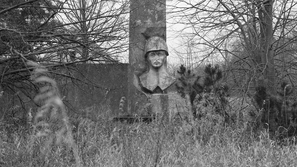 Schwarzweiß-Fotografie eines Kriegerdenkmals hinter Büschen: Ein anonymer Soldatenkopf blickt in die Ferne