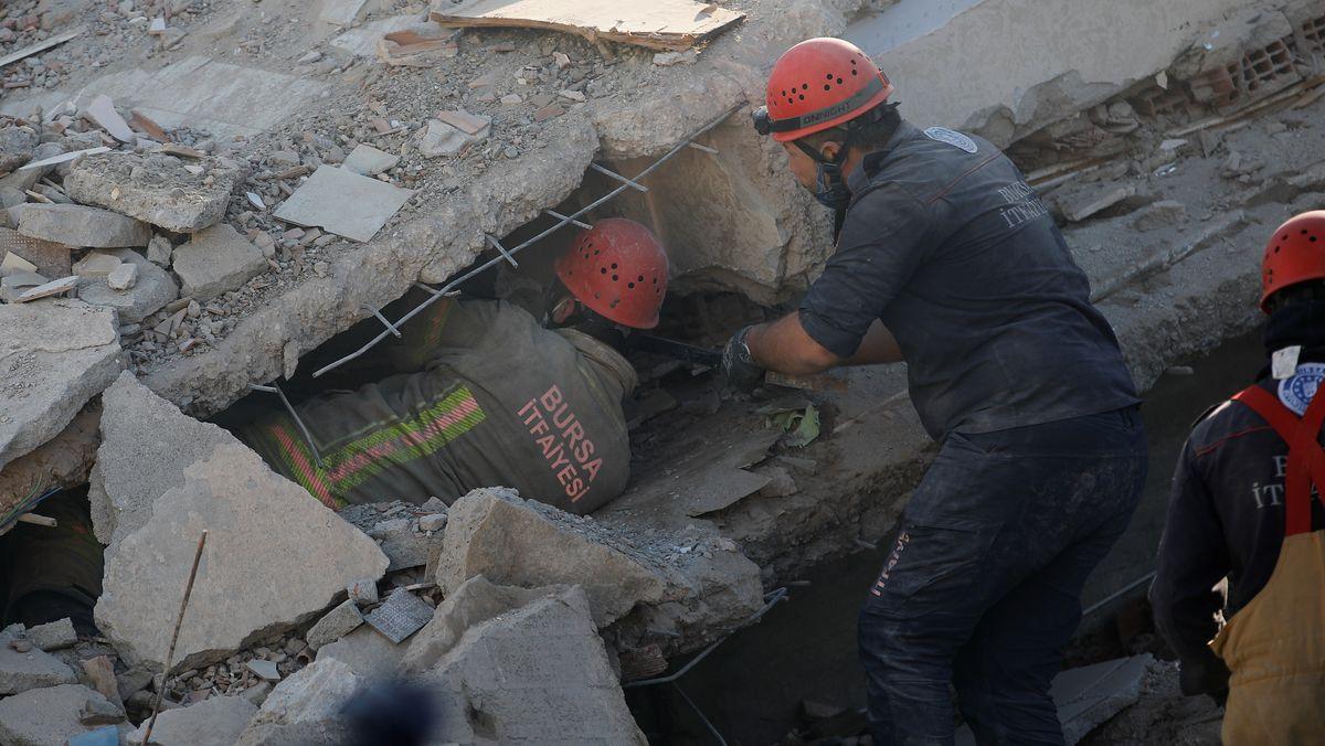 Helfer zwängen sich unter die Trümmer, um Verschüttete zu retten.