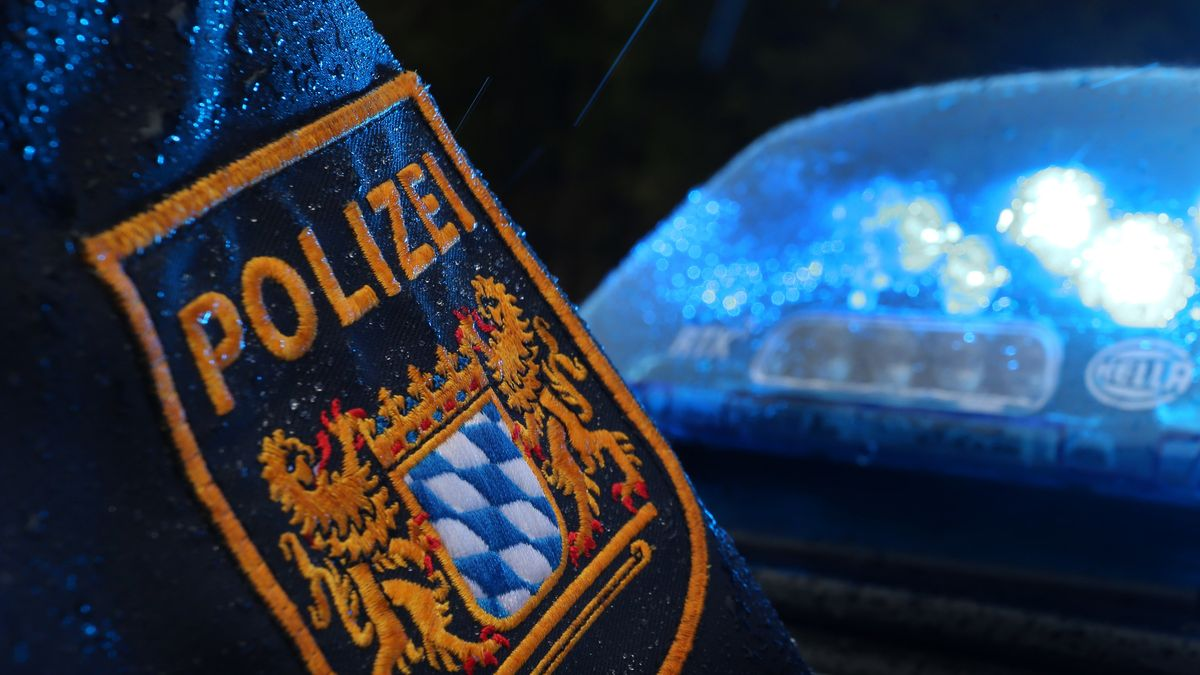 Ein Polizist steht im Regen vor einem Streifenwagen, dessen Blaulicht aktiviert ist (Symbolbild)