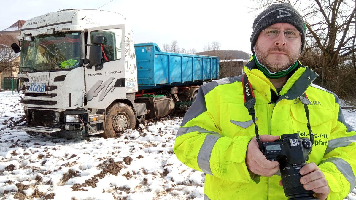 Der Unfallsachverständige Philipp Göpfert steht mit seinem Fotoapparat am Unfallort. Hinter ihm befindet sich der verbeulte Lkw auf einem Acker.