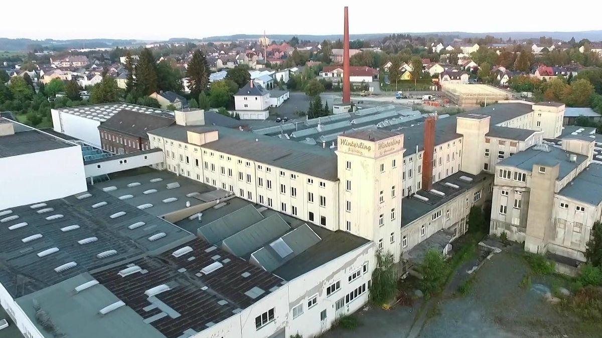 Die ehemaligen, etwas verfallenen Produktionsgebäude der Porzellanfabrik Winterling in Kirchenlamitz mit zwei roten Backsteinkaminen, aus der Vogelperspektive betrachtet.
