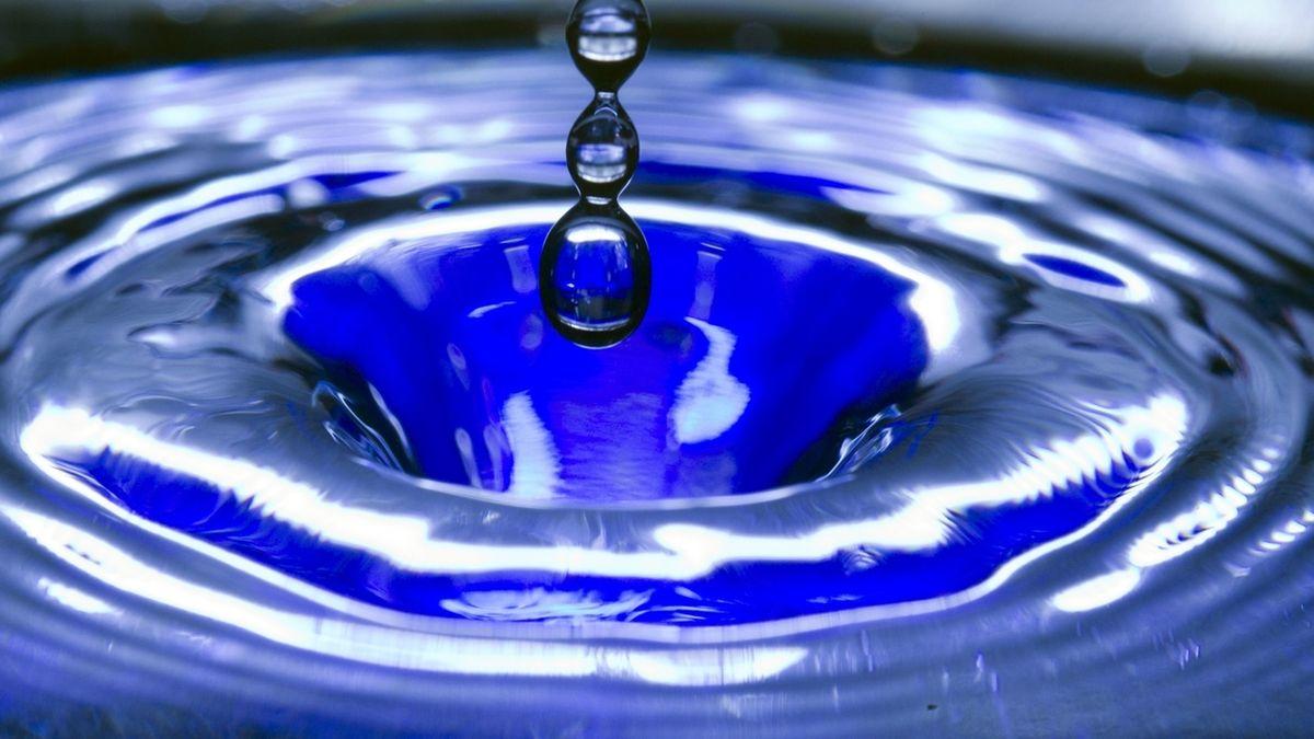 Ein Wassertropfen fällt in eine blaue Wasserschüssel (Symbolbild).