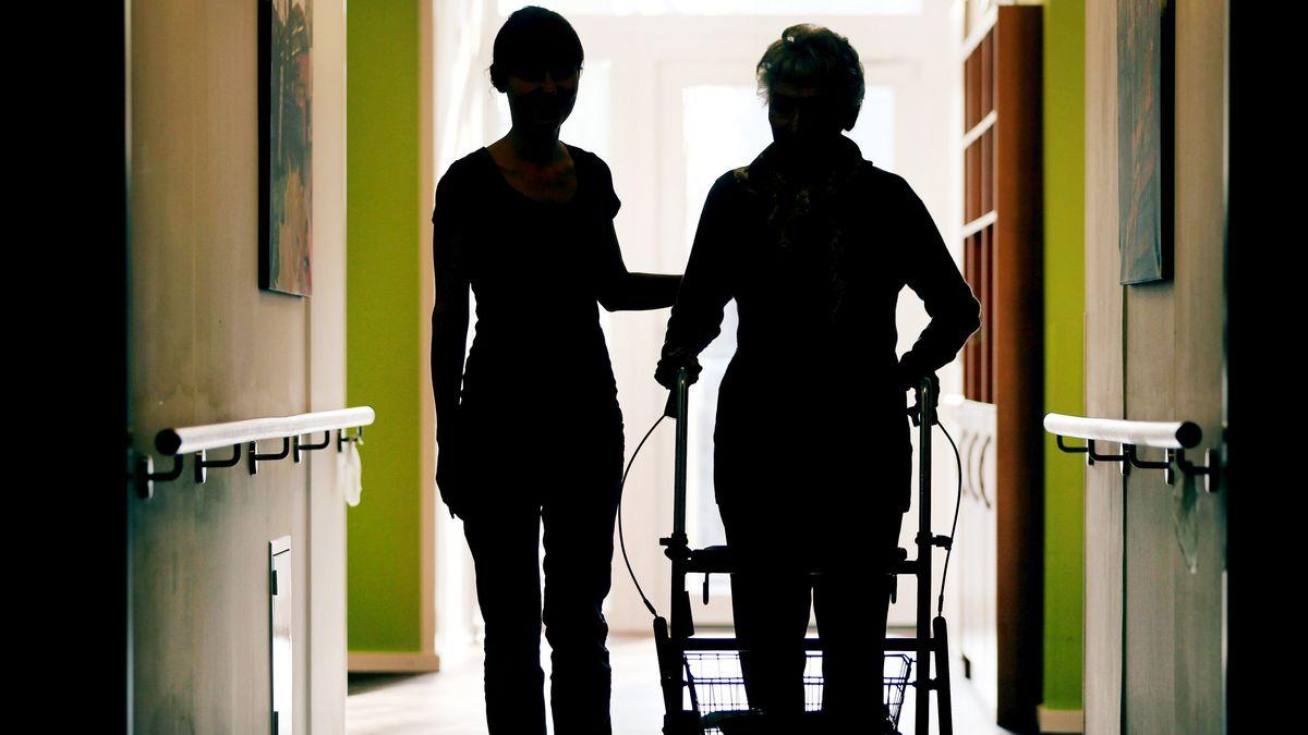 Eine Pflegekraft (l) begleitet die Bewohnerin eines Altenheims mit Rollator beim Gang durch den Flur.