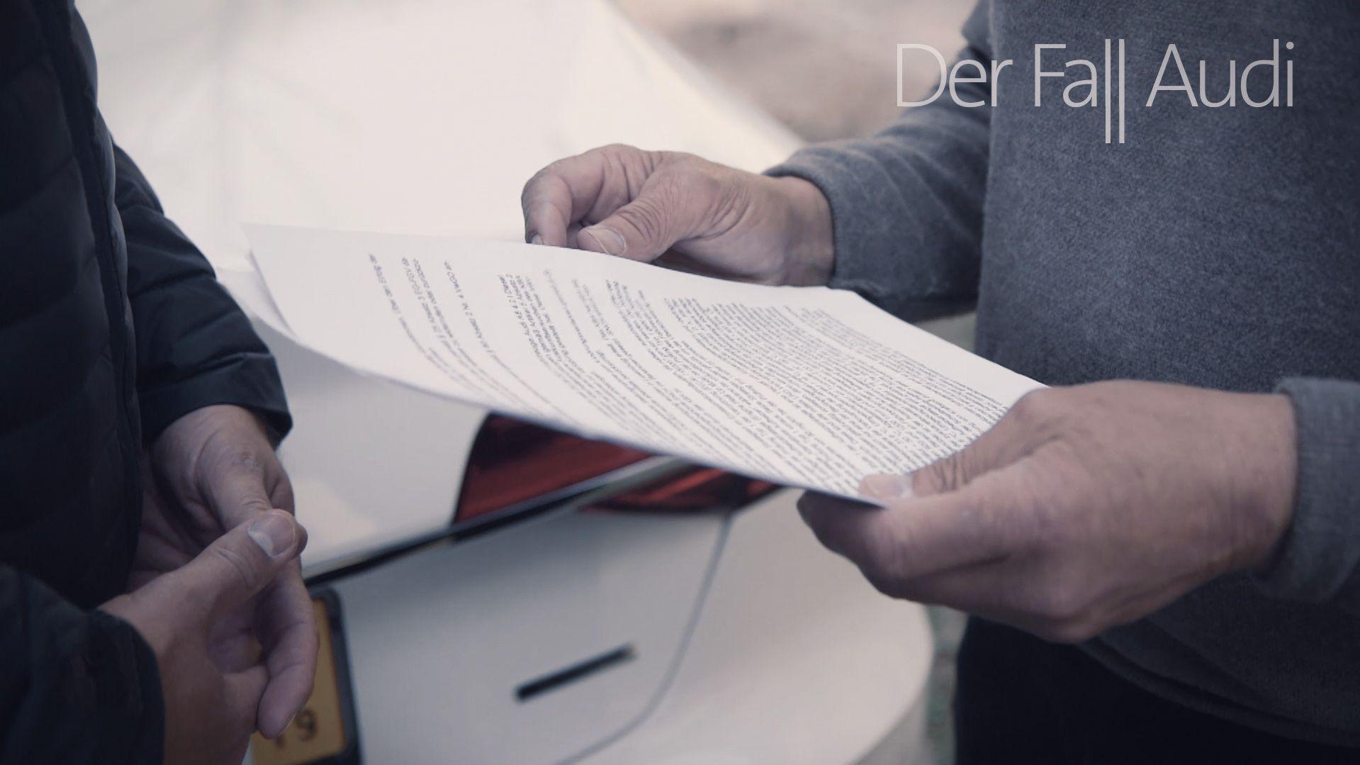 Ein Mann hält Dokumente in den Händen.
