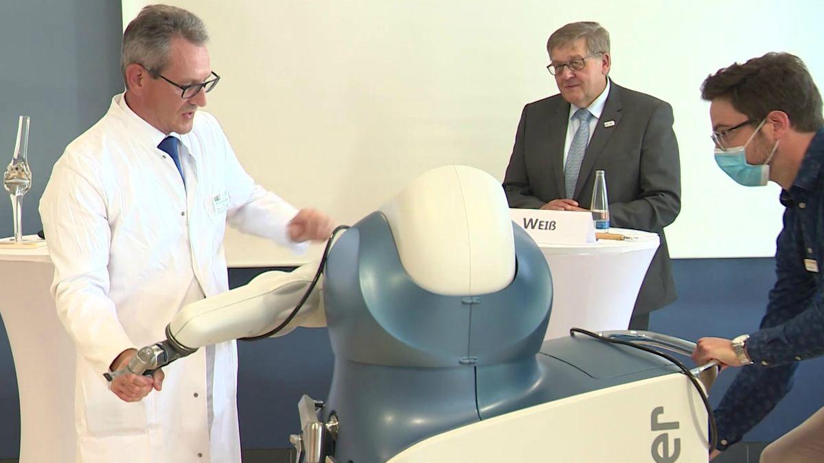 Mann in weißem Arztkittel stellt OP-Roboter vor.