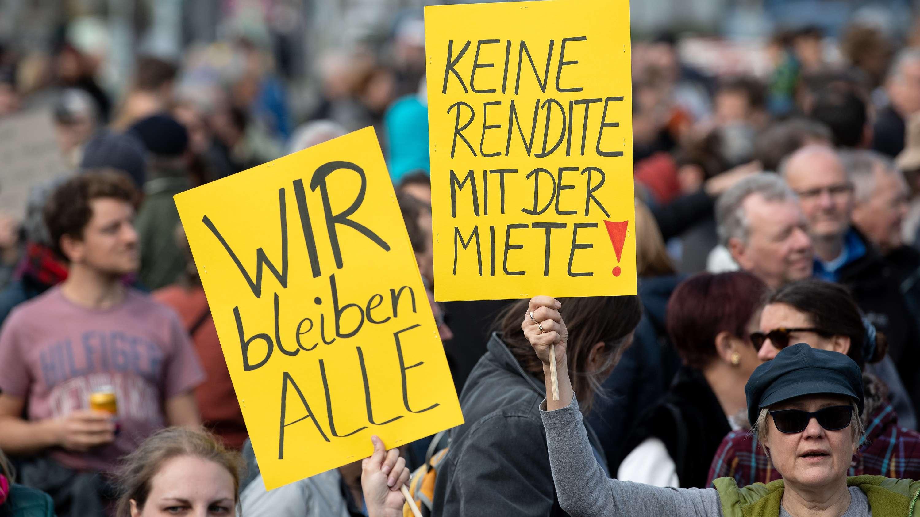 """Demonstranten halten in München Plakate mit der Aufschrift """"Wir bleiben Alle"""" und """"Keine Rendite mit der Miete"""" und protestieren damit gegen steigende Mieten"""