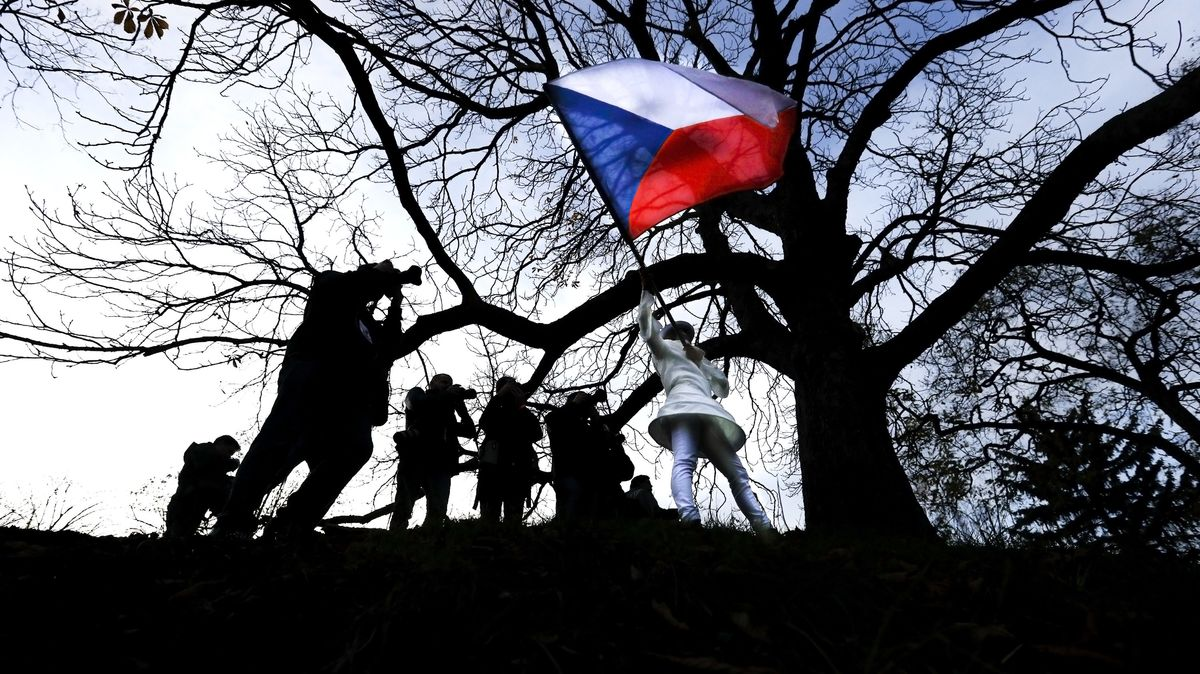 Eine kostümierte Tschechien schwenkt eine tschechische Flagge anlässlich des 30. Jahrestags der Samtenen Revolution.