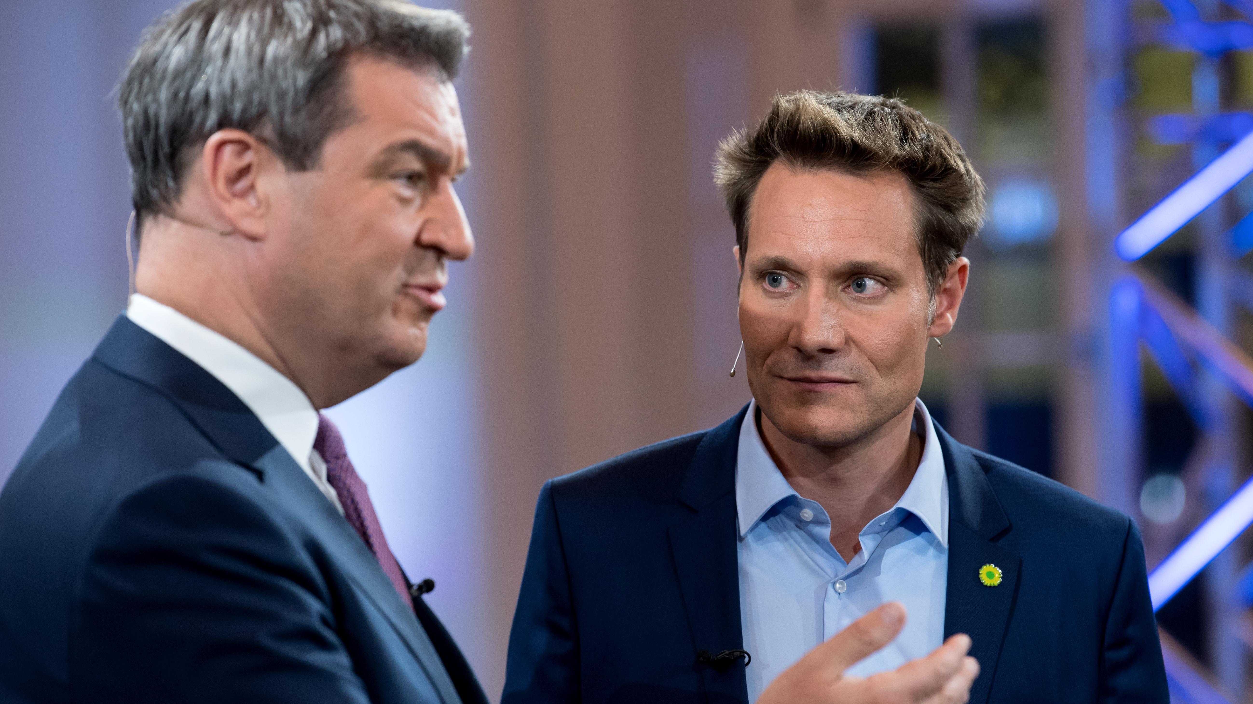 Markus Söder (l, CSU), Ministerpräsident von Bayern, und Ludwig Hartmann (Bündnis 90/Die Grünen), Fraktionsvorsitzender im bayerischen Landtag, stehen nach dem TV-Duell vor der Landtagswahl in einem Fernsehstudio des Bayerischen Rundfunks.