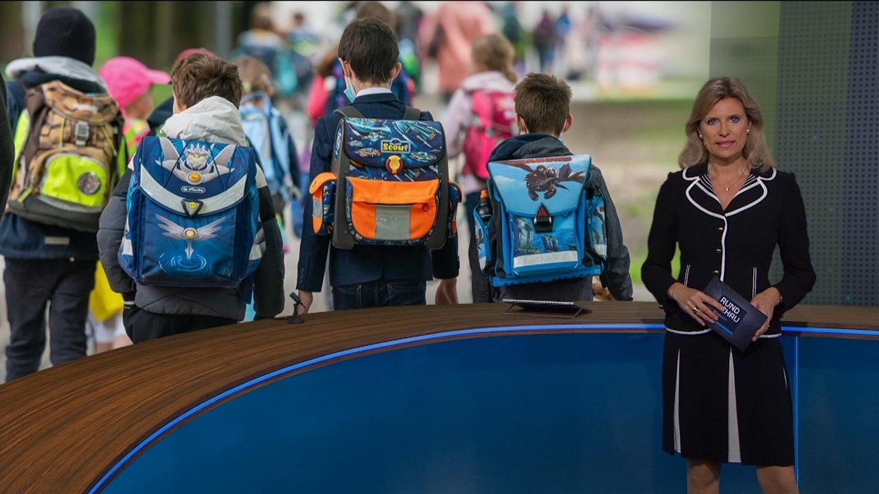 Anuschka Horn vor Bild mit Grundschülern mit Schulränzen