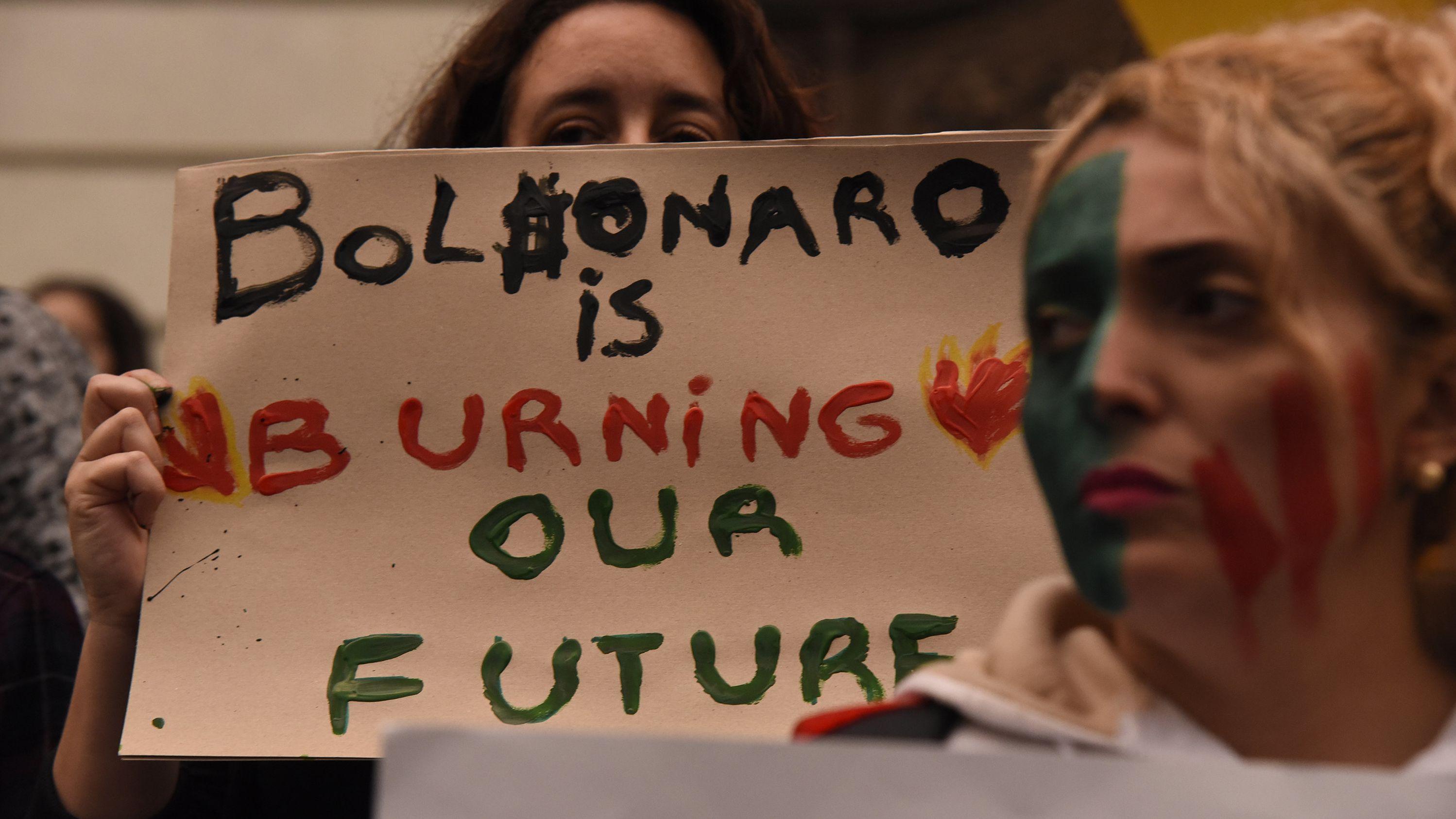 """Eine Frau hält bei einer Demonstration in Rio de Janeiro angesichts der verheerenden Waldbrände am Amazonas ein Schild mit der Aufschrift """"Bolsonaro ist burning our Future"""" (""""Bolsonaro verbrennt unsere Zukunft"""")."""