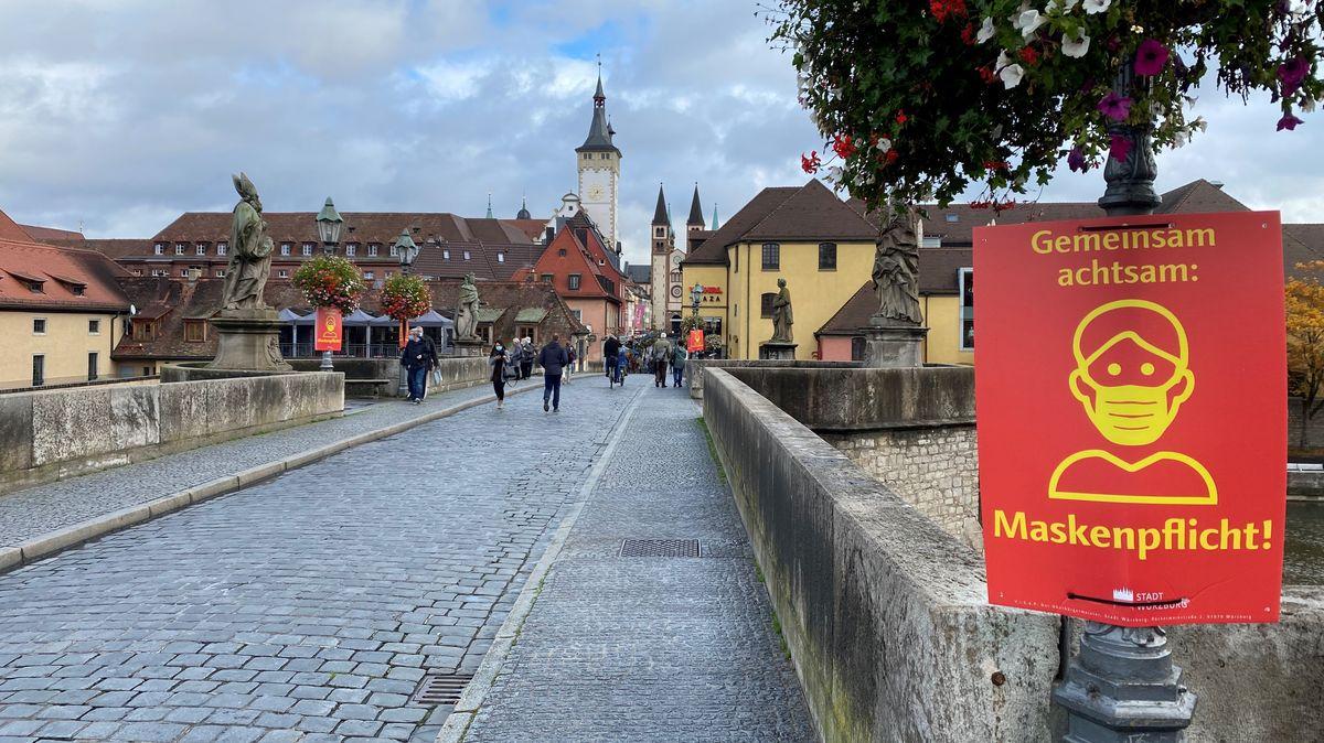 Auf der alten Mainbrücke in Würzburg hängen Schilder, die auf die Maskenpflicht hinweisen.