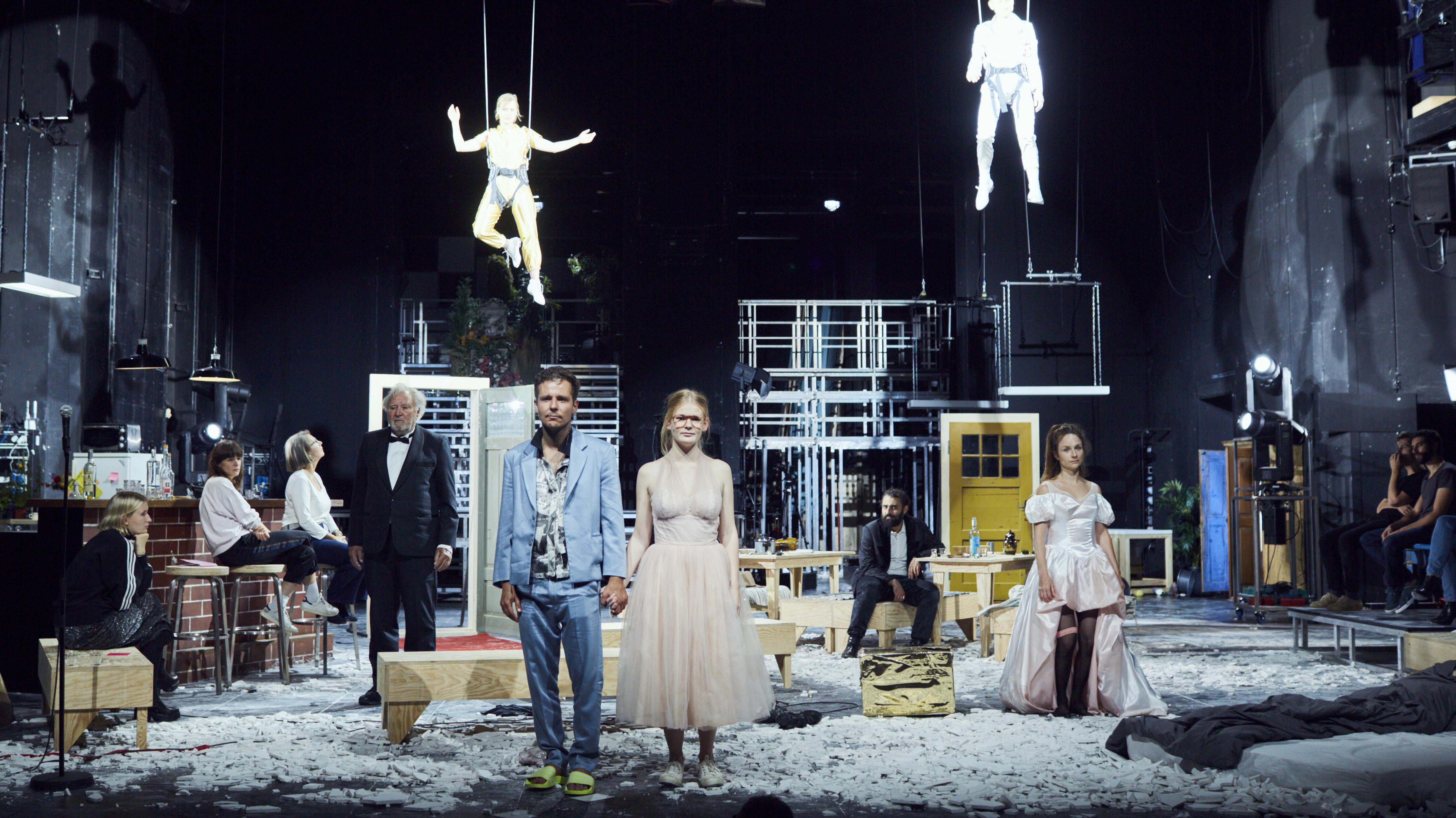 """Szene aus dem Theaterstück """"Dionysos Stadt"""": Ein Paar steht händchenhaltend im Vordergrund, im Hintergrund sitzen und stehen sechs Personen, an der Decke hängen zwei an Seilen."""