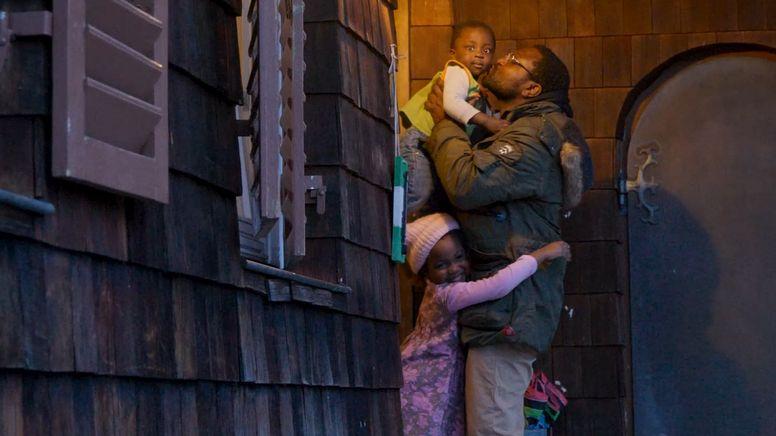 Edward Ebohon hält seine kleine Tochter auf dem Arm während die andere Tochter seine Beine umarmt. | Bild:ELKB