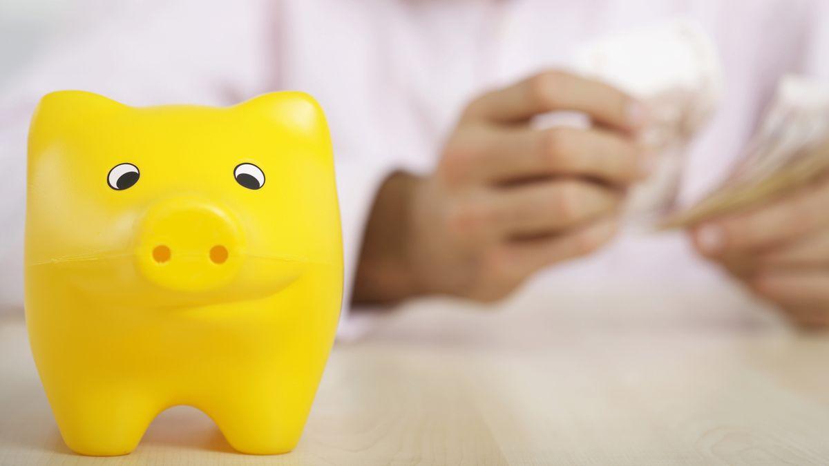 Ein gelbes Sparschwein vor einer Person, die Geldscheine in der Hand hält.