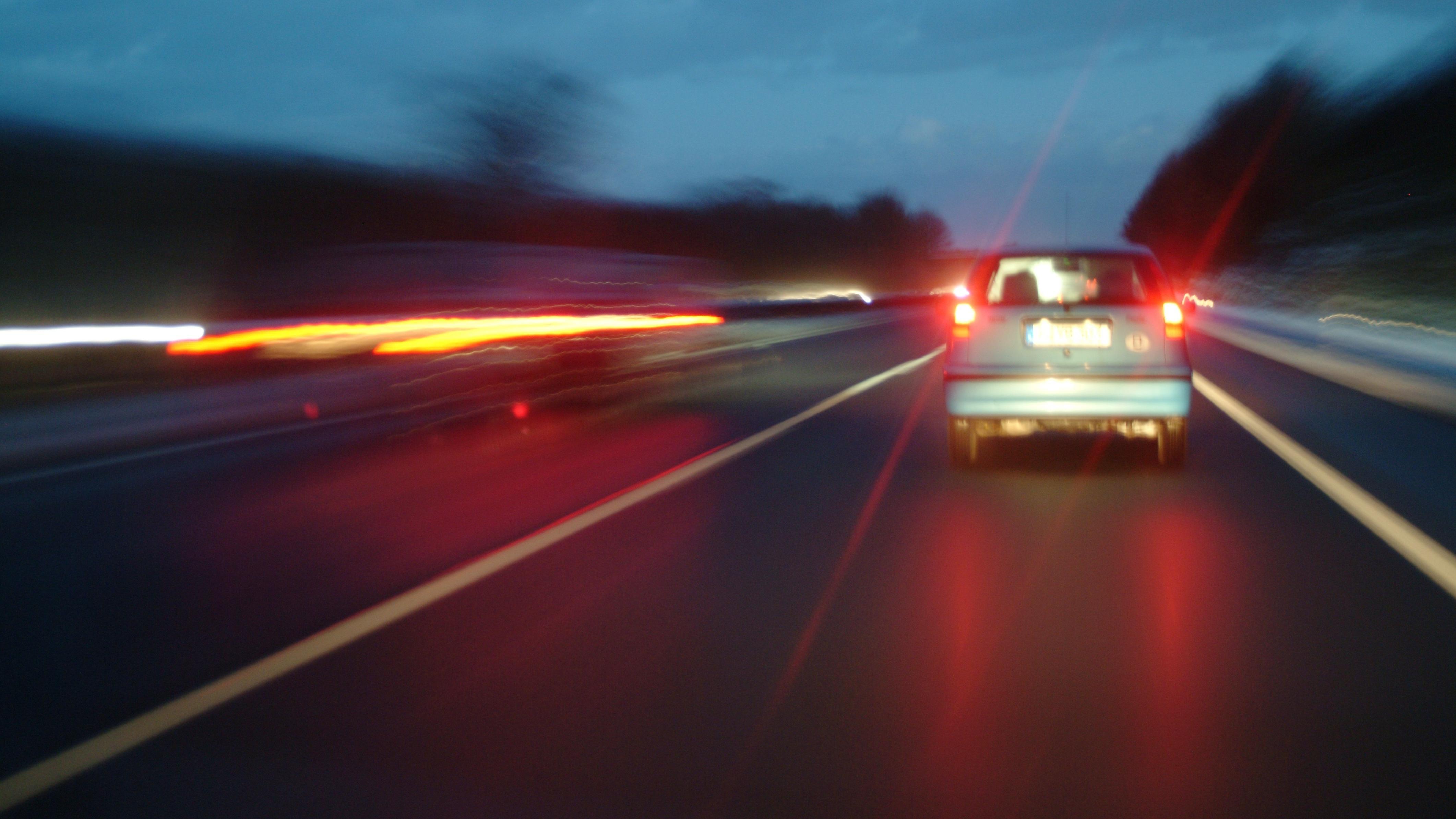 Auto überholt nachts auf Autobahn
