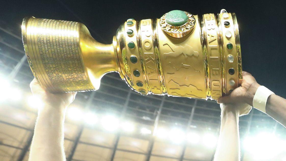 Nahaufnahme DFB-Pokal, drei Arme recken ihn in die Höhe.