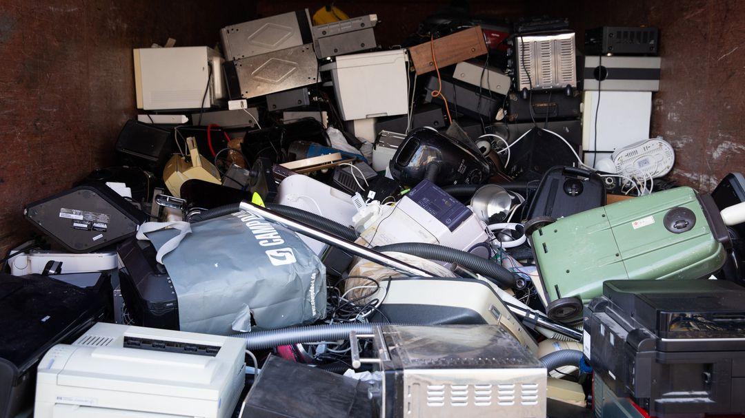 Defekte Haushaltsgeräte in einem Schrottcontainer.