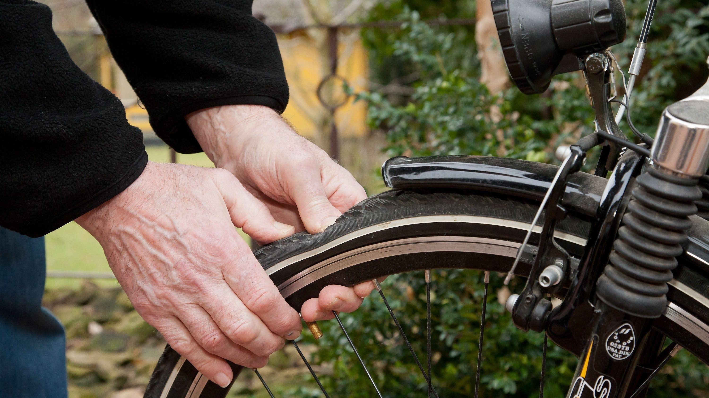 Fahrradcheck im Frühling: Ein Mann überprüft den den Luftdruck eines Fahrradreifens.