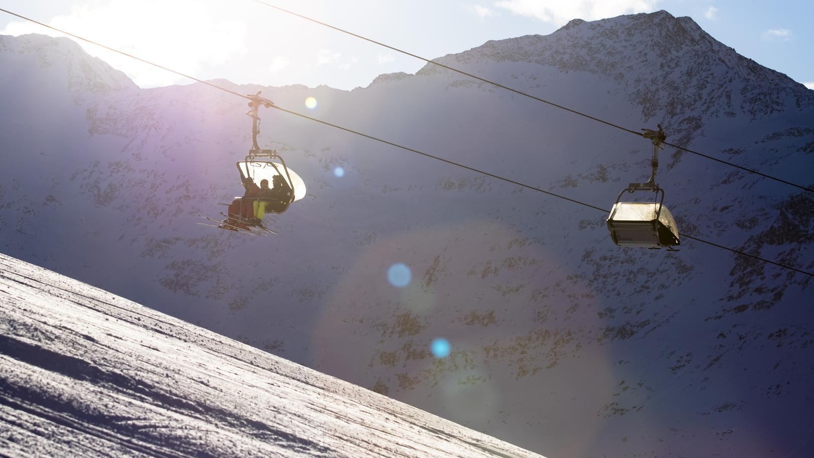 Skifahrer im Sessellift an der Skipiste