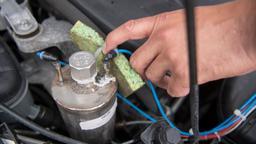 Hand zeigt in den Motor eines Diesels | Bild:picture-alliance