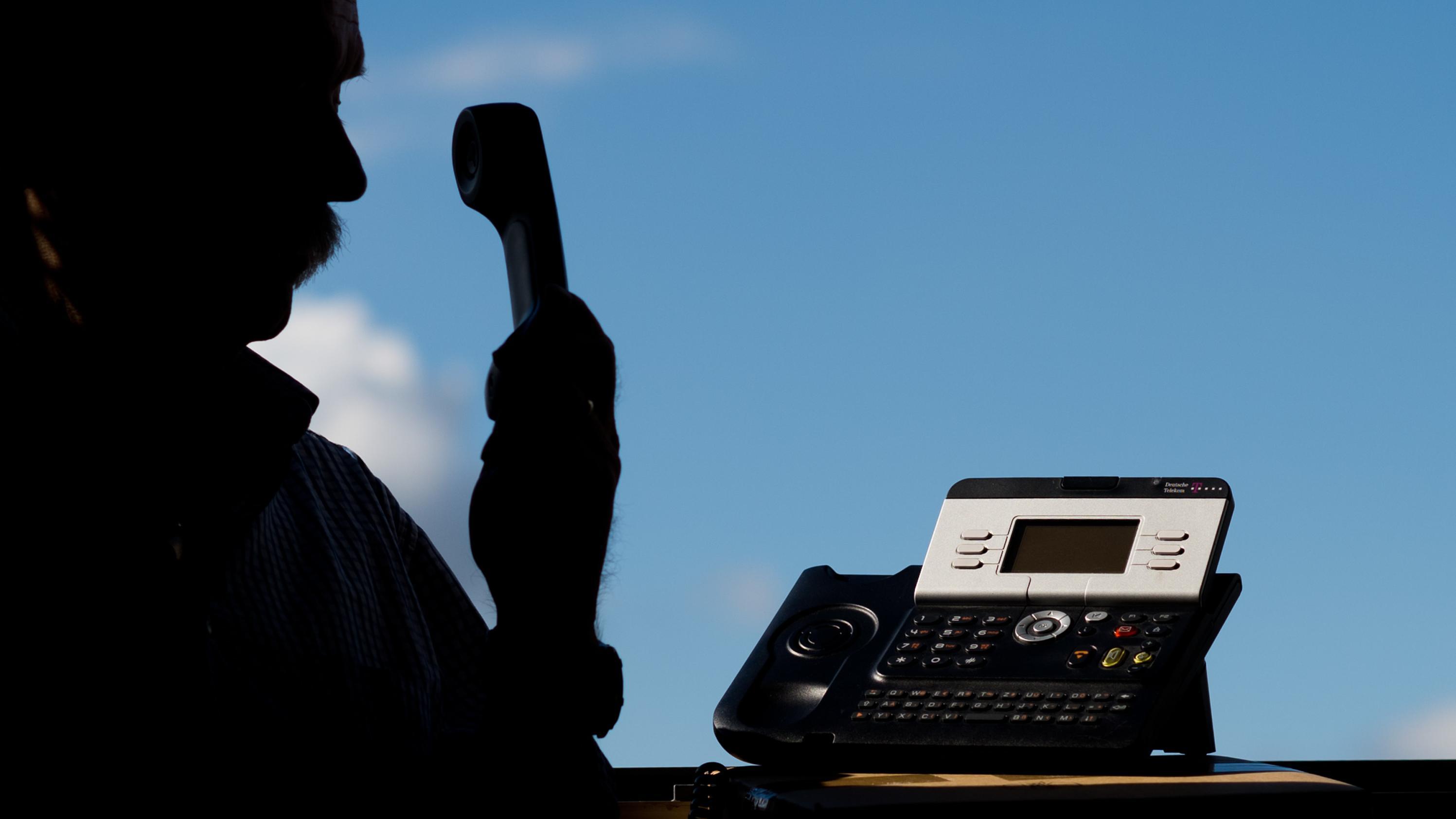 Ein Mann mit einem Telefon in der Hand (Symbolbild).